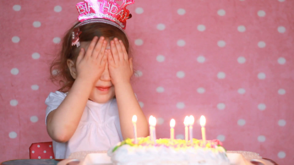 O atributo alt desta imagem está vazio. O nome do arquivo é videoblocks-happy-birthday-child-blows-out-candles-on-cake-at-party-and-make-a-wish-funny-little-girl-baby-pink-background_bb0zulijz_thumbnail-full01-1024x576.png